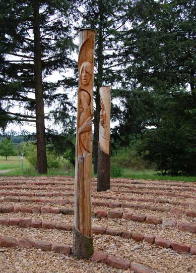 Labyrinth am Waldrand mit kunstvoll geschnitzten Holzstelen